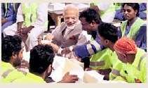 ISSUES: Narendra Modi with Indian labourers in Doha
